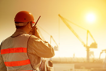 worker with large crane site and sunset background